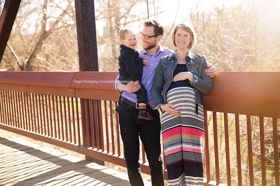 A family of three stands in the sunsine on an Edmonton footbridge