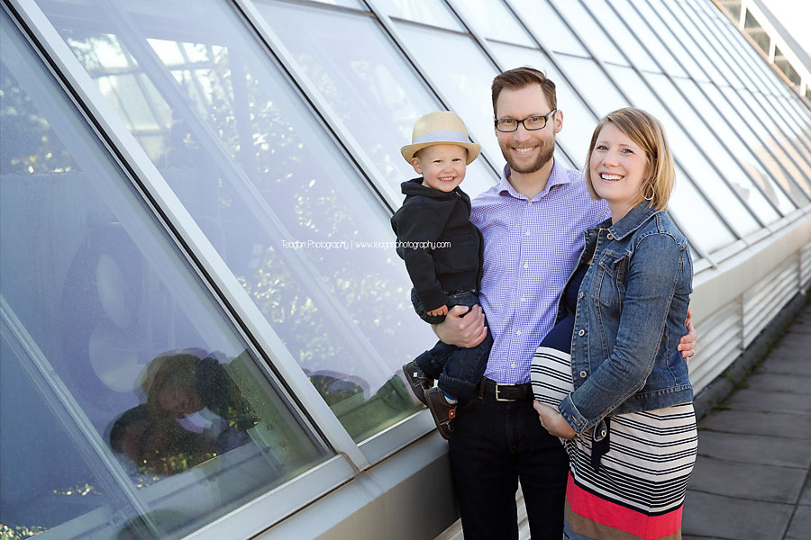 A family stands along the glass walls above the Muttart Conservatory Pyramids