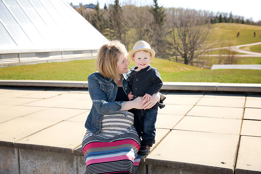 A little boy hugs his pregnant mom during an Edmonton maternity photo session