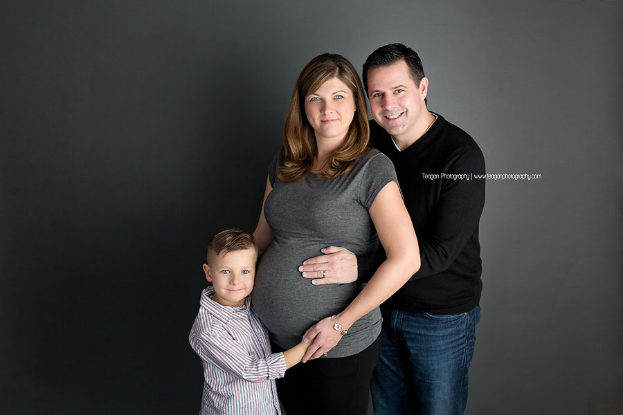 A family of three anticipates the arrival of twin boys during a studio maternity photography session in Edmonton