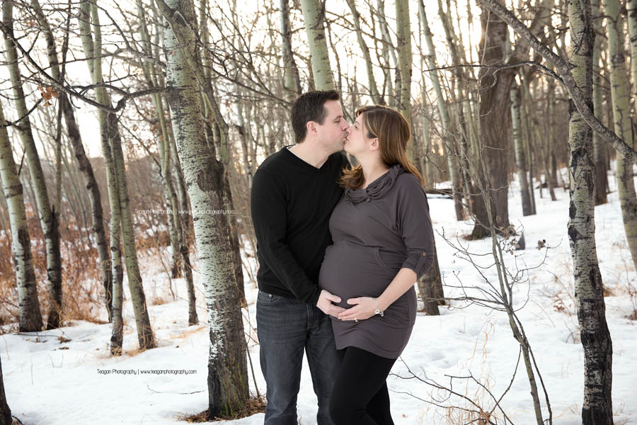 A pregnant couple kisses each other in a west Edmonton forest during their winter maternity family photography session