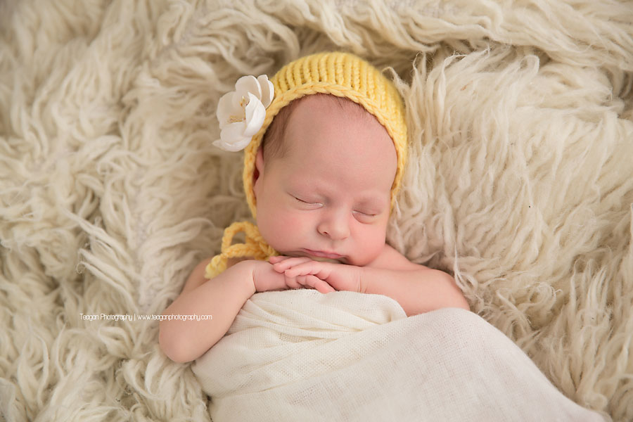 A newborn baby girl wears a butter yellow bonnet while sleeping on a cream coloured rug
