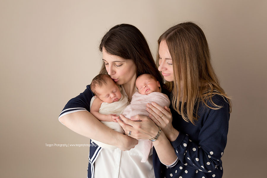 Adult sisters snuggle together with twin baby girls in Edmonton