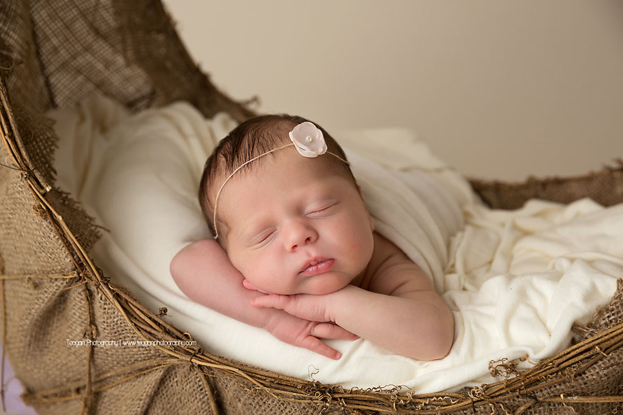 A newborn baby wearing a delicate flower in her hair sleeps while wrapped in a white blanket