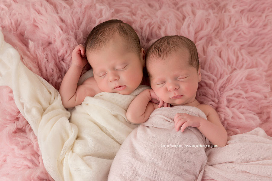 Twin baby girls sleep together on a pink fuzzy rug during an Edmonton twin newborn session
