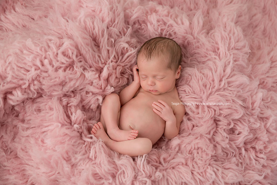 A newborn baby is curled up asleep on a pink fuzzy rugs