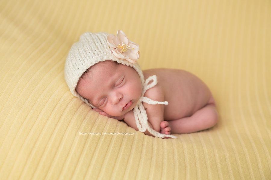 Asleep on a pale yellow blanket and wearing a white knit bonnett is an Edmonton newborn girl