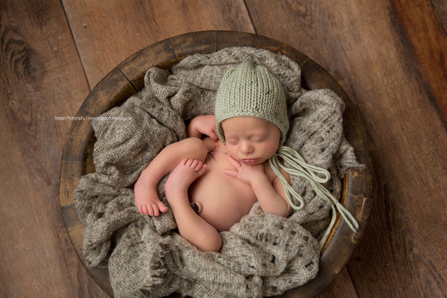 A little baby boy is curled up in a grey blanket and wearing a green knit hat