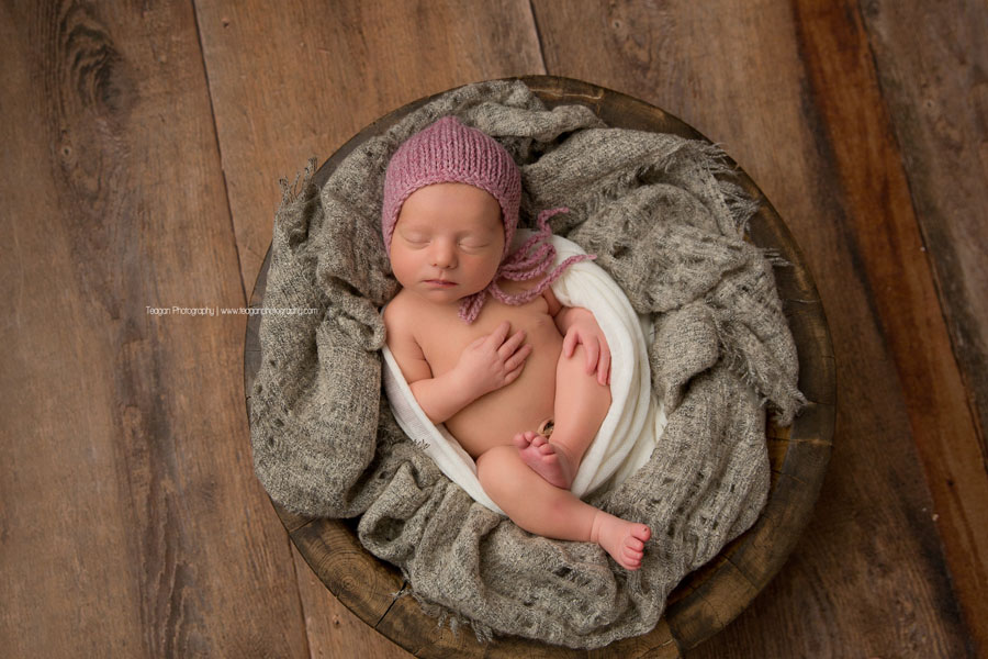 A tiny newborn girl wearing a rose pink knit bonnet sleeps curled up in a blanket in a wooden bowl