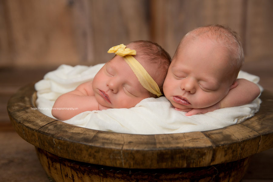 Newborn twins in Edmonton sleep in a wooden bowl together