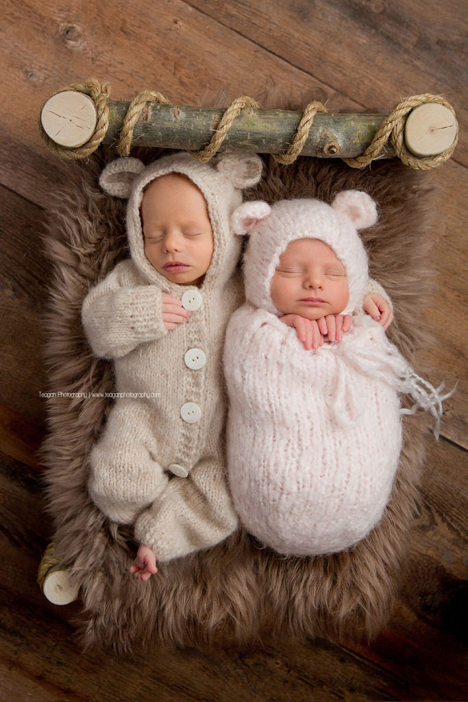 Wearing a teddy bear outfit is a newborn boy snuggling his twin sister