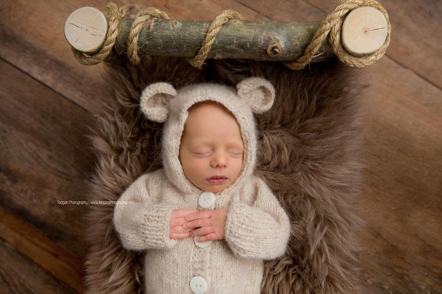 A newborn boy sleeps in a cream coloured teddy bear costume