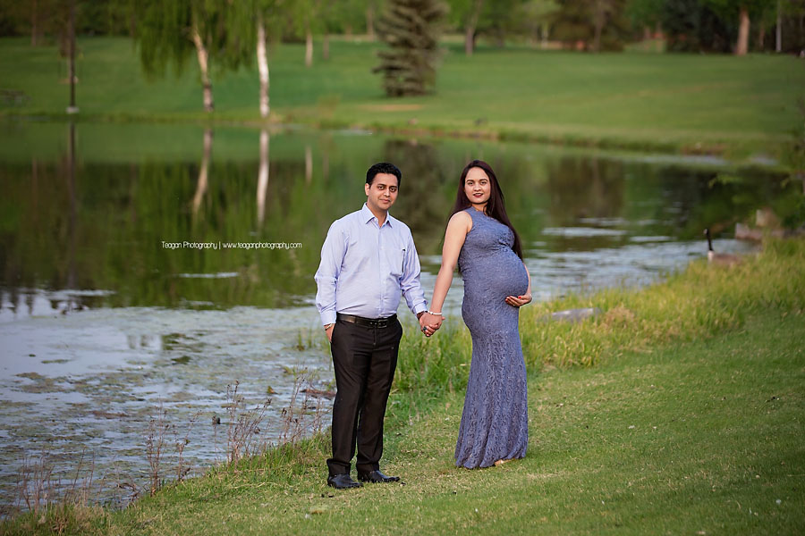 a pregnant couple of East Indian heritage pose together in front of the lake at Hawrelak Park in Edmonton