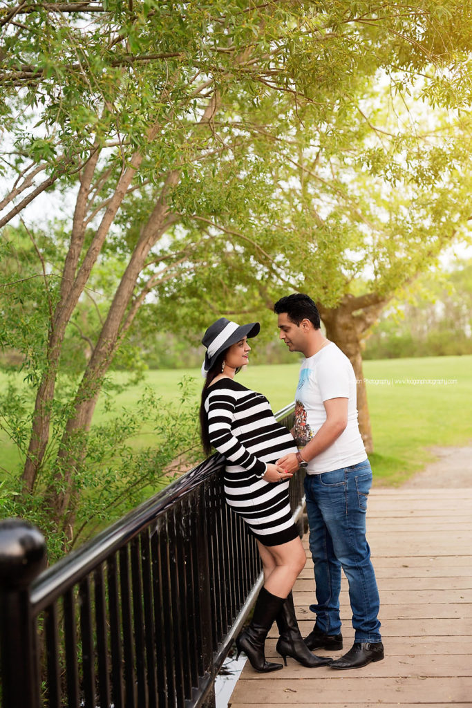 Wearing a white and black striped maternity dress is an hindu woman holding her black hat on a black metal bridge.