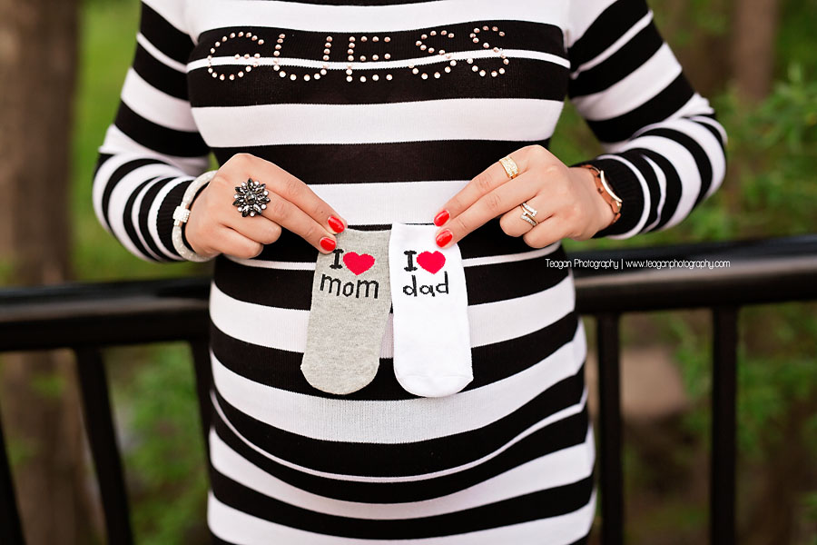 A pregnant mom holds tiny little socks to her belly