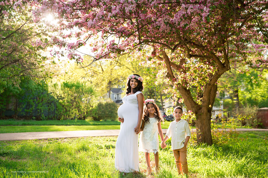A pregnant mother poses with her two children underneath a blossoming crab apple tree in the Edmonton River valley