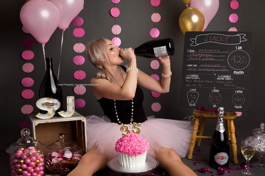 A birthday girl drinks directly out ot the champagne bottle during her adult cake smash photo shoot in Edmonton