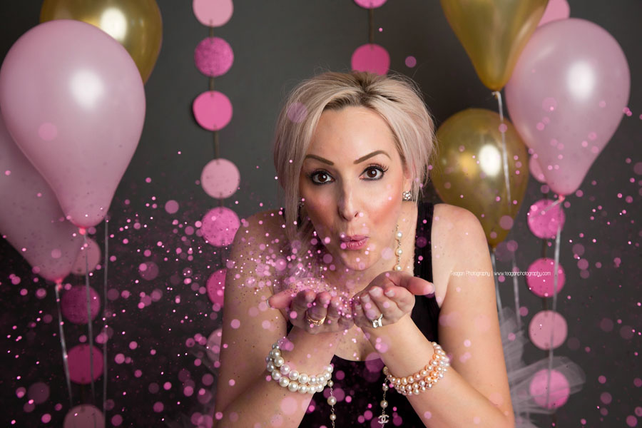 A blonde woman blows pink glitter during her adult cake smash photos in Edmonton