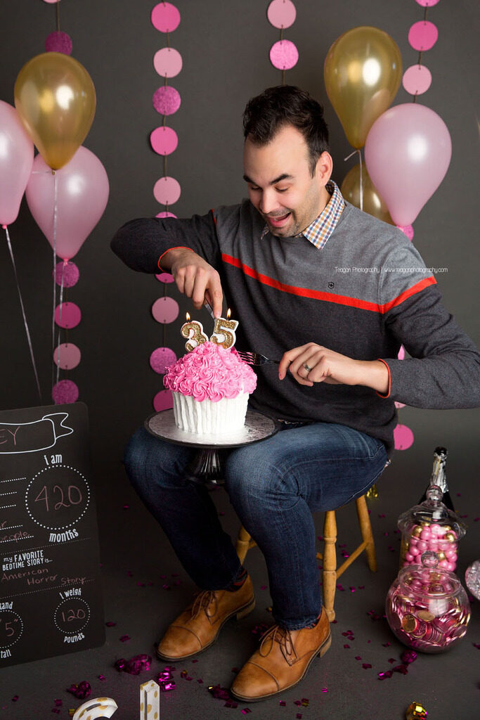 The husband of a woman sneaks in to steal some of her cake during her Edmonton cake smash photo shoot
