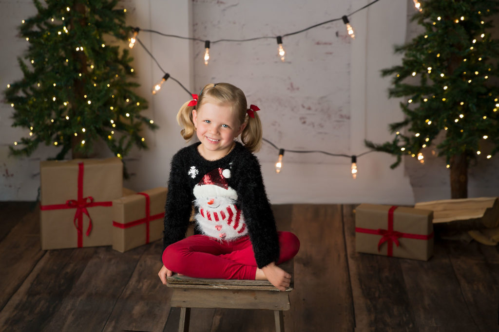 A cute blonde girl wears a snowman sweater during a Christmas mini photography session in Edmonton.