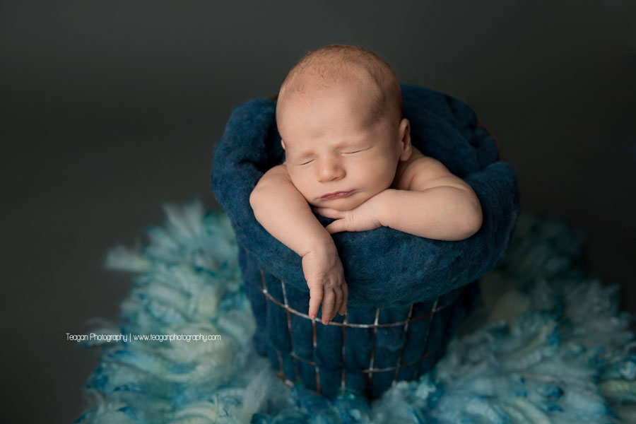An Edmonton newborn boy sleep in a bucket with a blue blanket