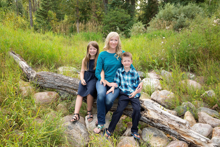 A mother sits on a wooden log with her two school age children during an Edmonton family photography session
