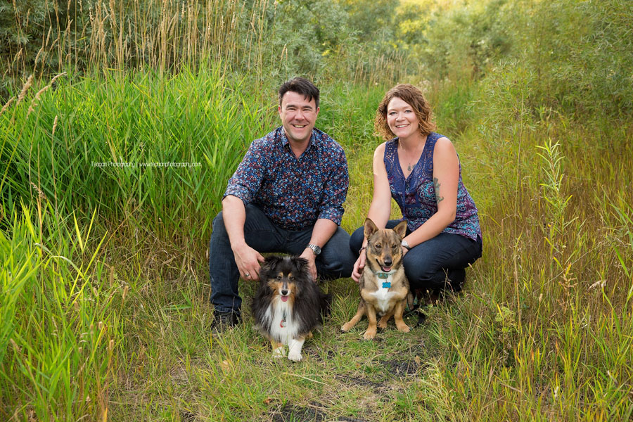 A husband and wife crouch in long grasses with their two small dogs