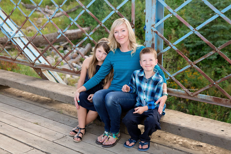 A mother hugs her two school age children during an Edmonton family photography session on a metal blue bridge