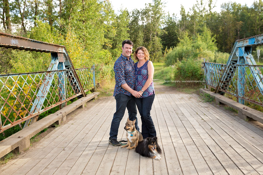 A husband and wife stand on a blue metal bridge with their two small dogs