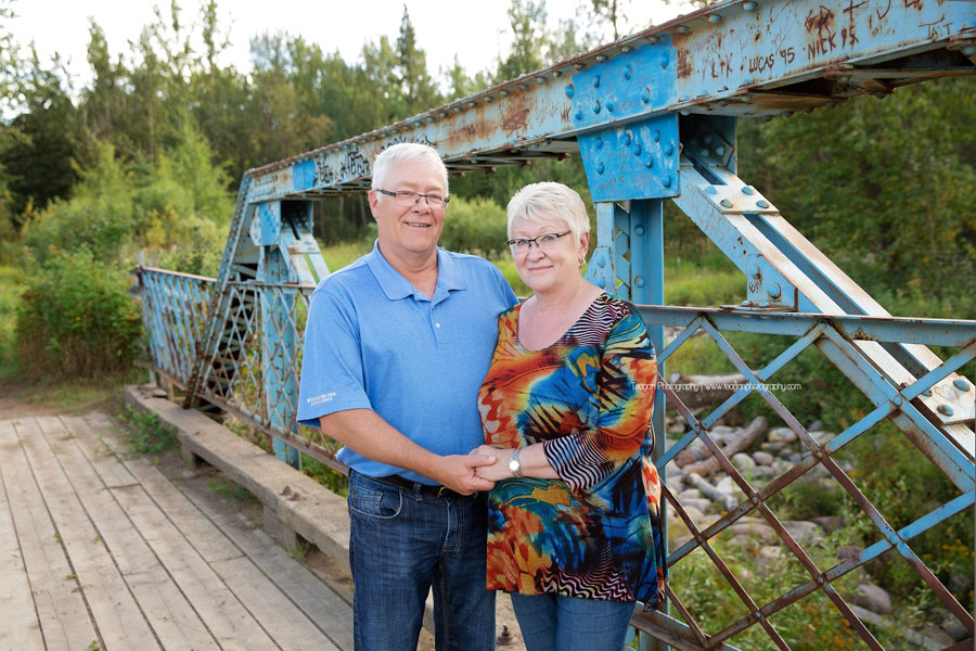 A senior couple stand together on the blue bridge at Larch Sanctuary