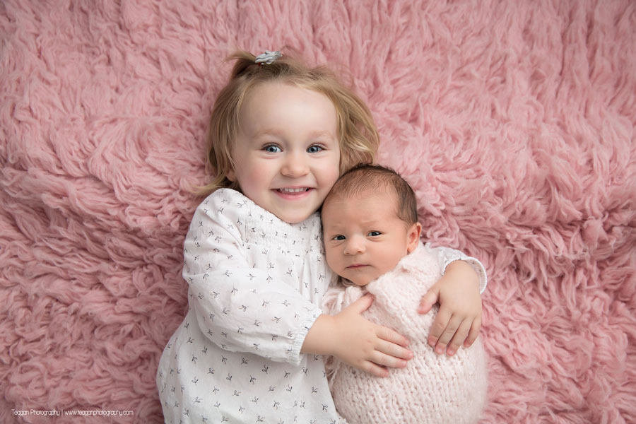 A blonde toddler hugs her newborn baby sister