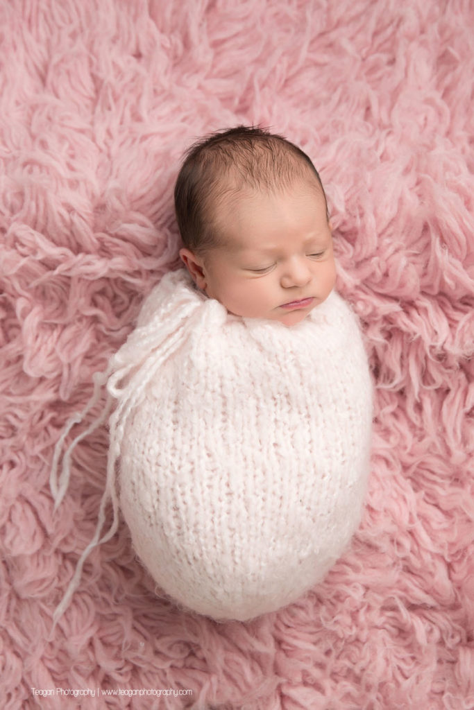 An Edmonton newborn baby sleeps on a pink rug in a pink scarf