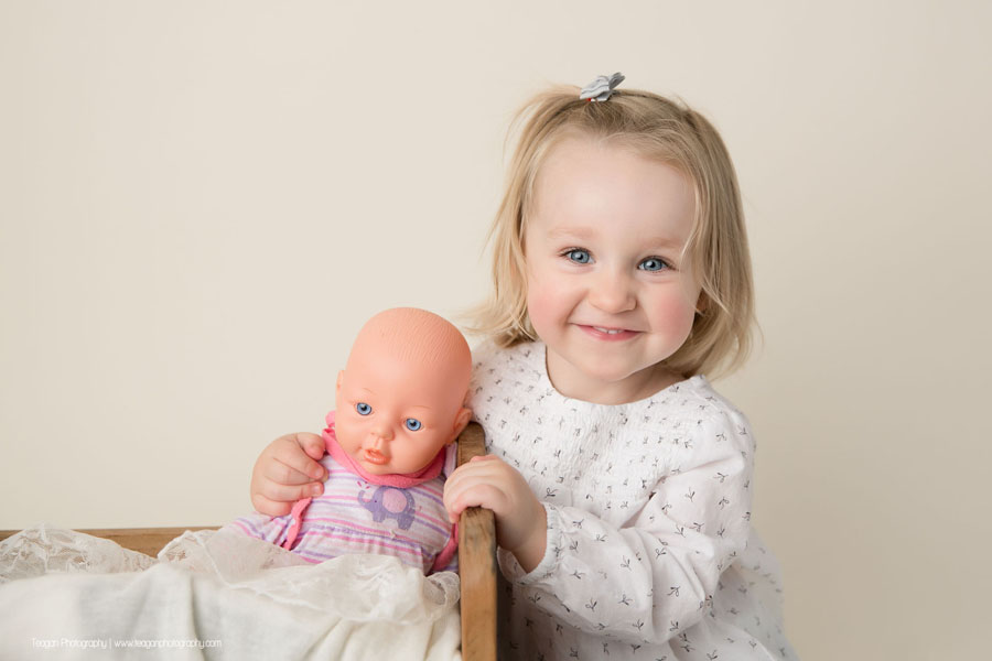A blonde toddler with blue eyes hugs her baby toy