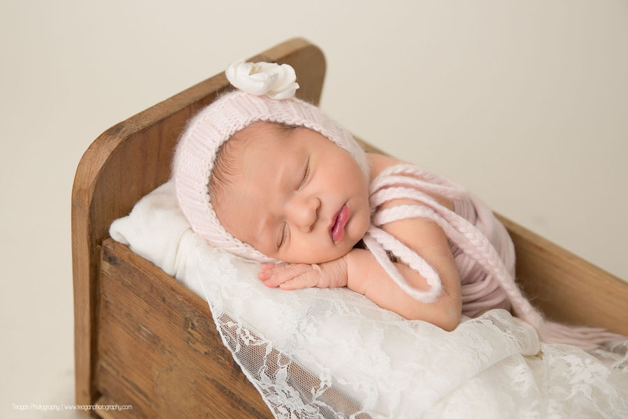 With her hand tucked under her cheek is a sleeping baby girl in a pale pink knit bonnet