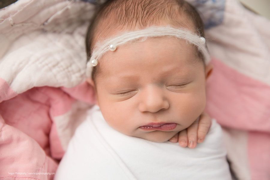 wrapped in white is a sleeping newborn baby girl with her hands tucked underneath her cheek