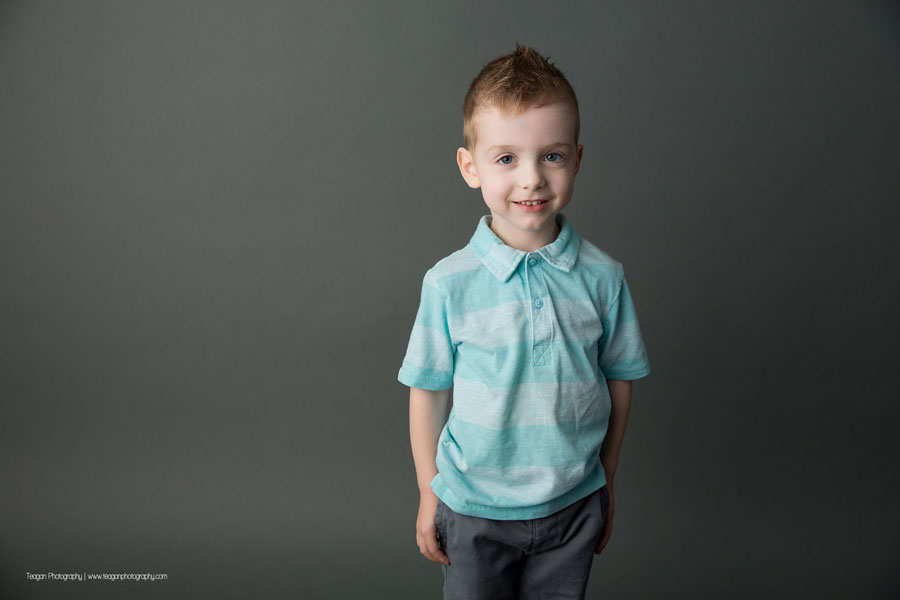 A preschool boy stands in front of grey wall with his hands in his pockets
