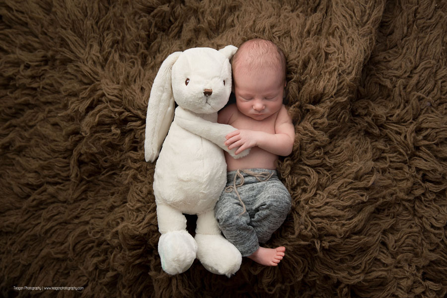 A newborn boy hugs a white rabbit toy while he sleeps