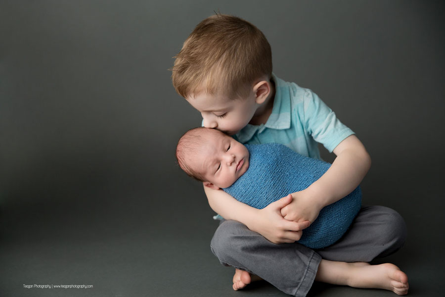 A big brother kisses his baby brother during an Edmonton newborn photography session