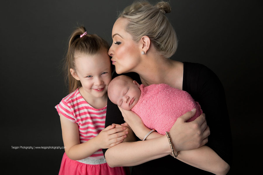 A mother cuddles with her two daughters during an Edmonton newborn photography session