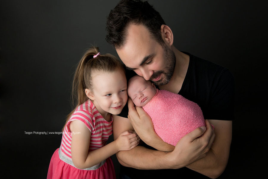 A father cuddles with his two daughters during an Edmonton newborn photography session
