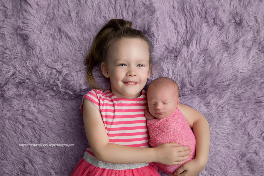 a big sister wearing matching pink clothes holds her newborn sister on a lilac purple rug