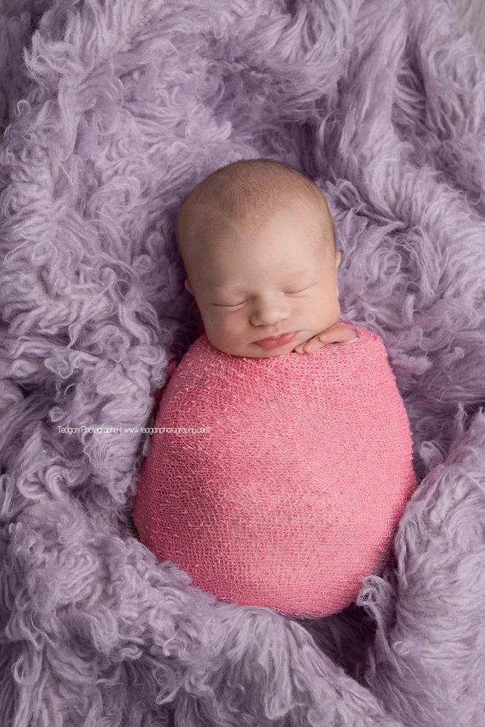 a newborn baby girl wrapped in pink sleeps on a lilac rug