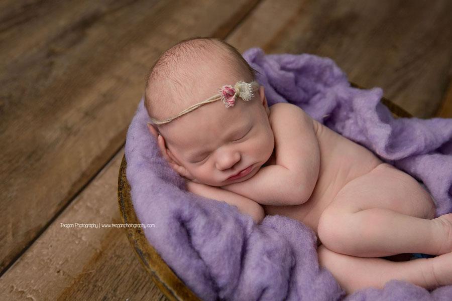 A newborn girl sleeps in purple fluff during an Edmonton newborn photography session