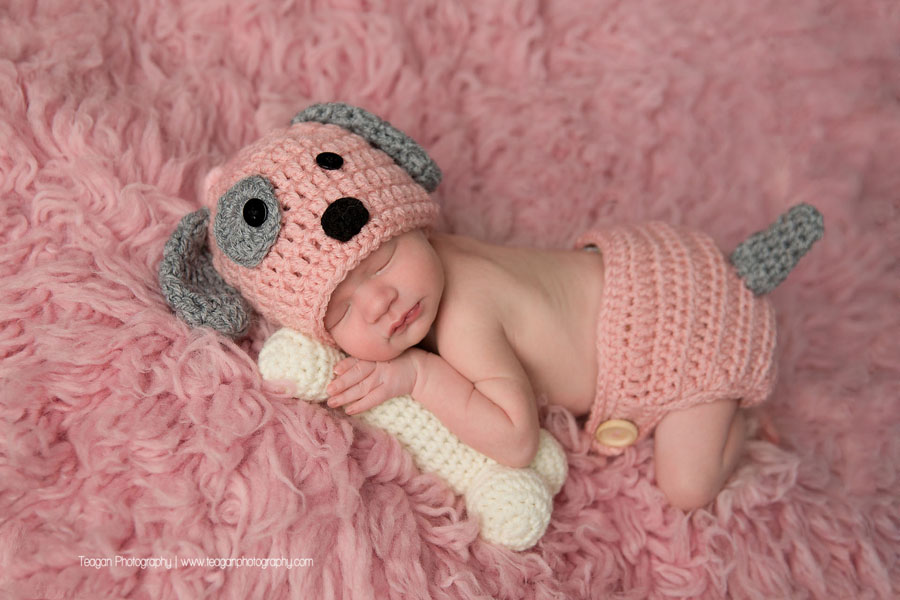 A baby girl is wearing a pink knit puppy bonnet while holding a knit dog bone