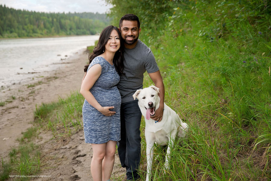 An expectant couple pose with their large white dog during an Edmonton photography session