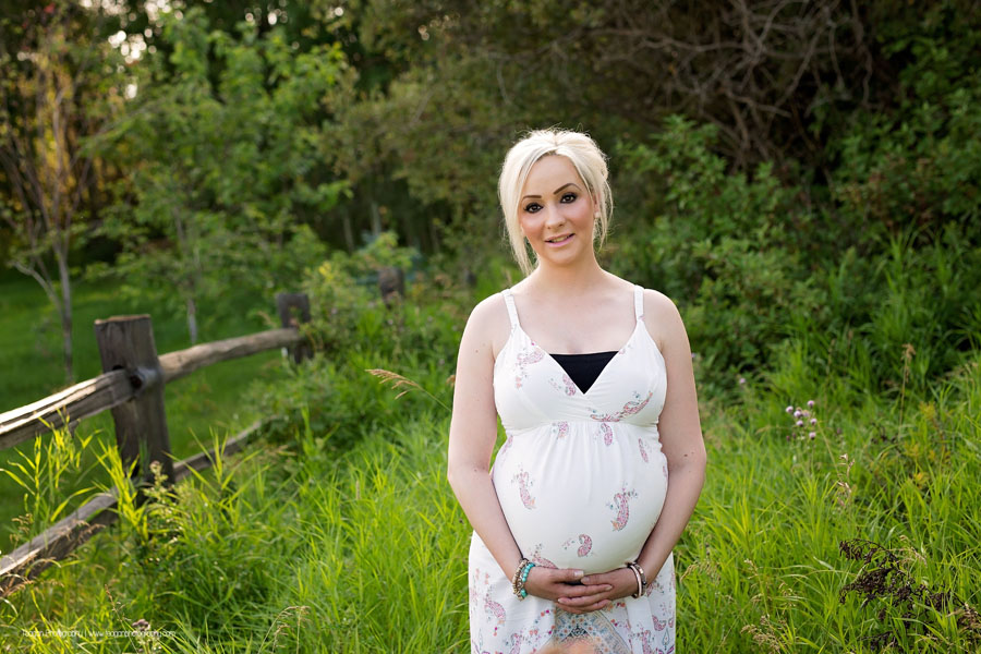 A blonde haired woman wearing a white maternity sun dress hugs her pregnant belly