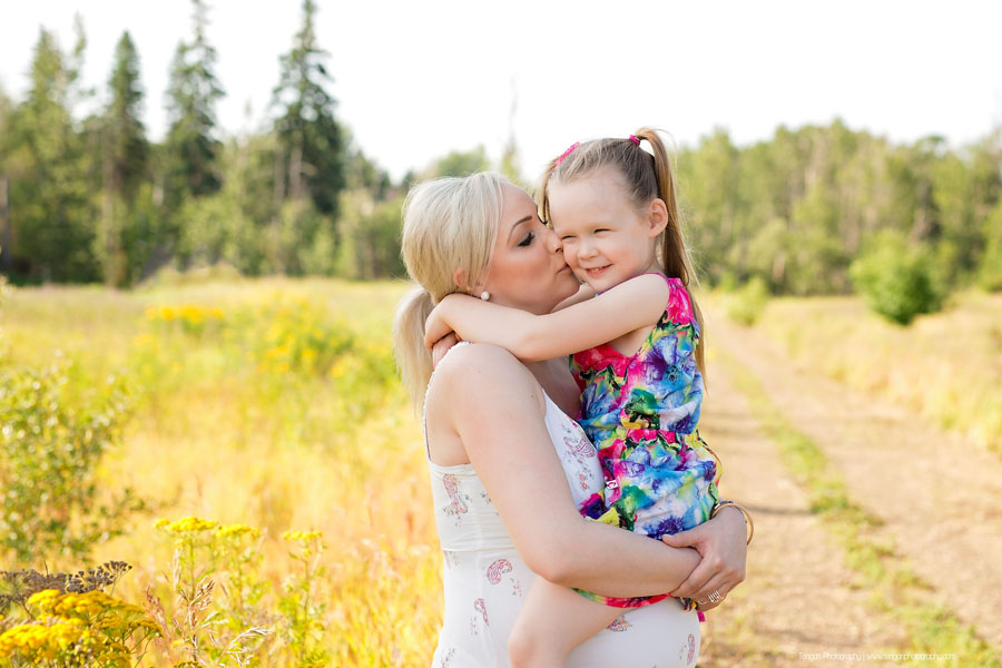 A mother kisses the cheek of her preschool age daughter