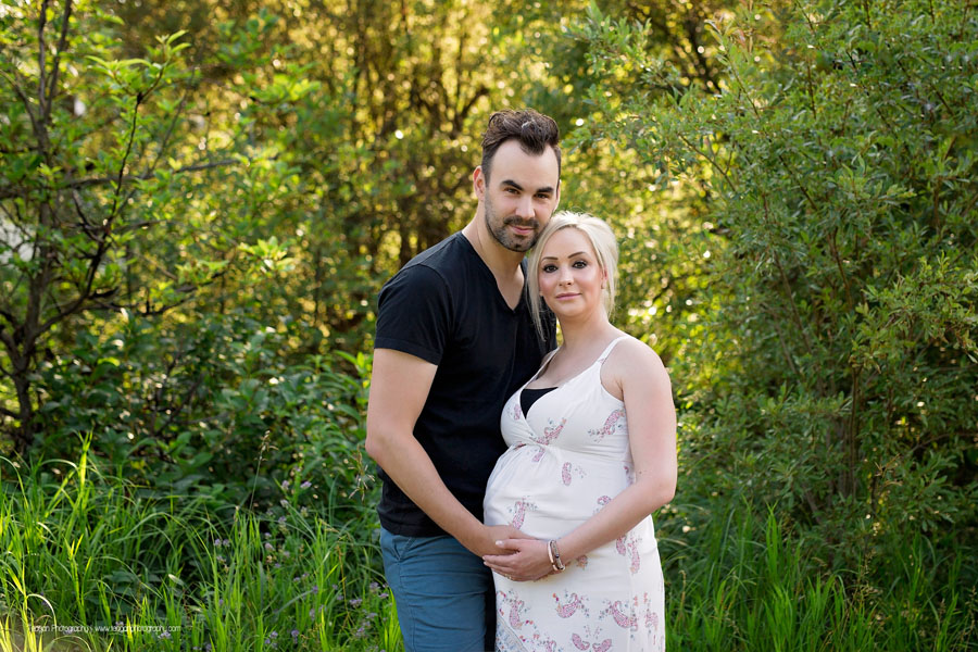 A husband and wife hug each other in a Sherood Park field during a maternity photography session