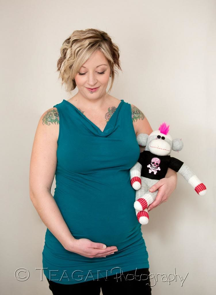 Holding a rock and roll styled sock monkey, hugs her pregnant belly