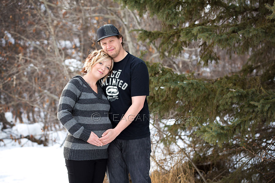 A husband cuddles with his pregnant wife in Red Willow Park in St Albert